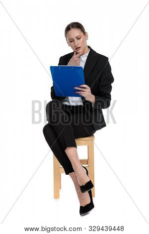 elegant businesswoman wearing black suit sitting and reading something on clipboard intrigued against white studio background