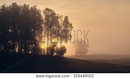 Silhouette Of A Hunting Tower At The Edge Of The Woods At Sunrise.