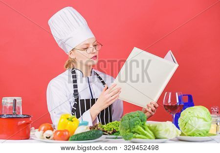 Cooking And Serving Healthy Vegetarian Menu. Pretty Female Cook Reading Menu Card At Kitchen Table.