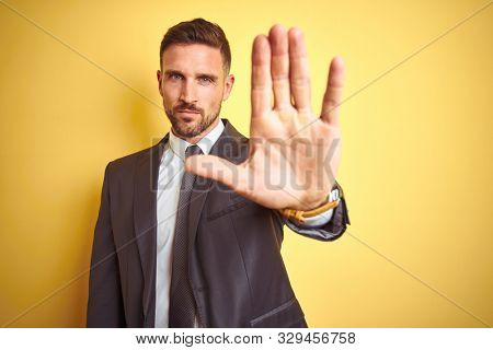 Young handsome business man over yellow isolated background doing stop sing with palm of the hand. Warning expression with negative and serious gesture on the face.