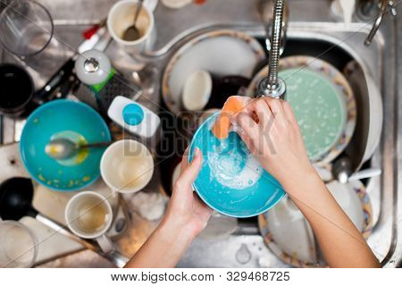 Girl Washes A Dirty Plate On The Background Of The Sink With Dirty Dishes, Top View