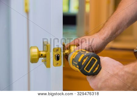 Closeup Of A Professional Locksmith Installing Or New Lock On A House Door Handle With Screwdriver