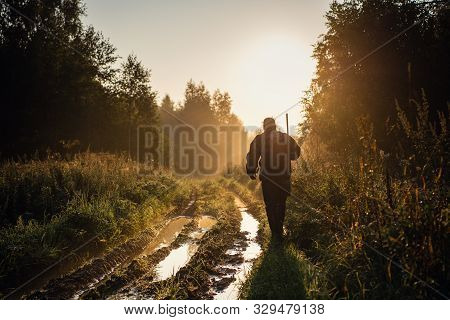 Vintage Hunter Walks The Forest Road. Rifle Hunter Silhouetted In Beautiful Sunset Or Sunrise. Hunte