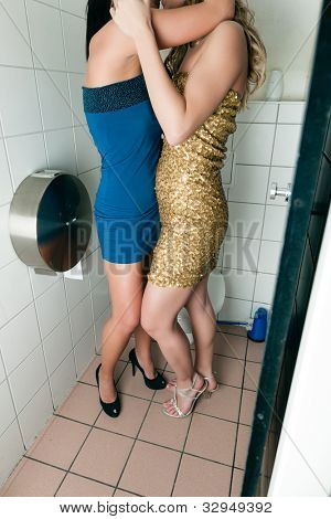 Two women kissing in the toilet of a club or disco