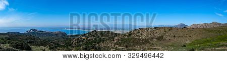 Mountain landscape in Roses, Catalunya, Spain. Mountain covered with green grass and shrubs on blue sky and sea background. Panoramic view, natural background. The bay and the city in the background. poster