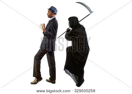 Man In A Grim Reaper Halloween Ghost Costume Having Fun And Scaring A Grown Businessman In A Suit.
