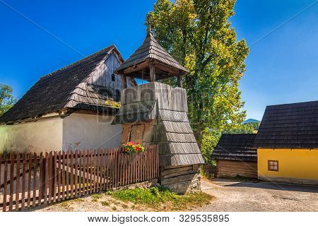 A Wooden Bell Tower On A Street With Ancient Colorful Houses In Vlkolinec Village, Slovakia, Europe.