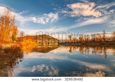 Mirroring Autumn Landscape In The Vah River Near The Zilina Town, Slovakia, Europe.