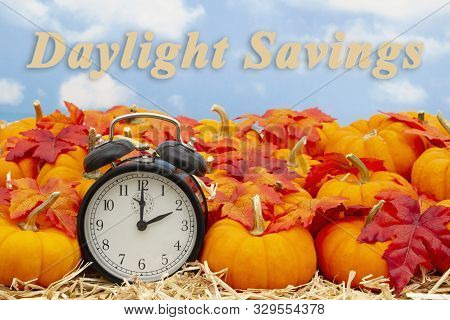 Daylight Savings Time Change Message With A Retro Alarm Clock With Orange Pumpkins With Fall Leaves