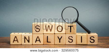 Wooden Blocks With The Word Swot Analysis And A Magnifying Glass. The Method Of Strategic Business P