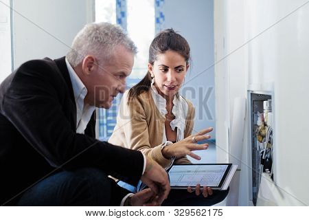 Architect Showing Heating System To Assistant In Construction Site