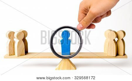 A Magnifying Glass Looks At A Leader Stands On The Scales Between Two Groups Of People. Resolving Co
