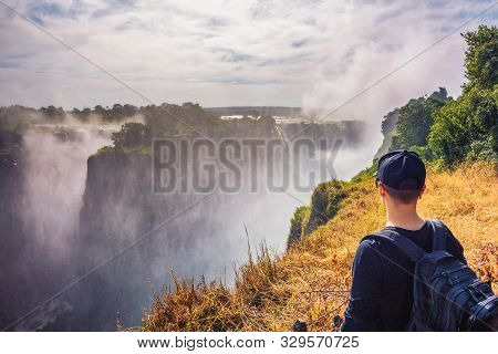 Tourist With A Backpack Looks At The Victoria Falls On Zambezi River Located At The Border Of Zambia