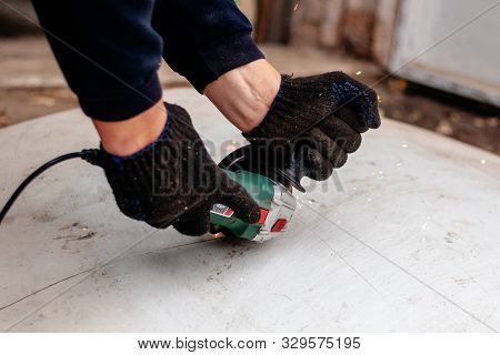 A Man Works With An Angle Grinder. Cuts Metal.