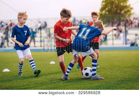 Kids Kicking Football Ball. Boys Play Soccer On Grass Field. Spectators Parents In The Background. Y