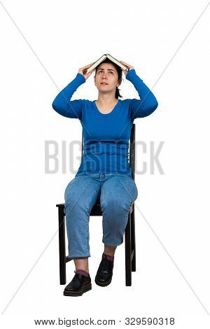 Confused Woman Student, Seated On A Chair, Keeps Open Book Over Head Isolated On White. Difficult Ta