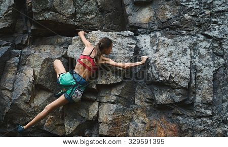 Sports Woman With Slim Fit Body Climbing On The Rock, Having Workout, Climber Makes A Hard Move.