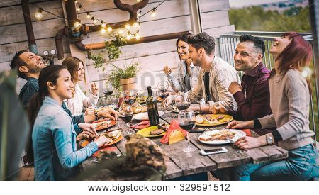 Young People Dining And Having Fun Drinking Red Wine Together On Balcony Rooftop Dinner Party - Happ
