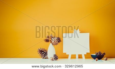 Composition Of Dried Flowers, Thorns In Light Vase, Pine Cones And Blank Canvas On A Stand On Ocher