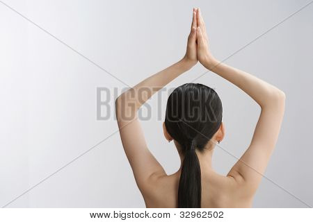 Rear view of Asian woman with hands over head