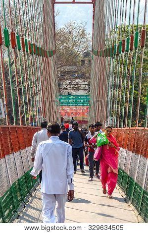 Rishikesh, India - Circa April 2018. Bridge Over Ganga River, Ram Jhula, Rishikesh. People Crossing