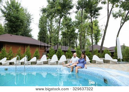 Happy Caucasian Couple Sitting Near White Chaise Longue, Swiming Pool And Wooden House.