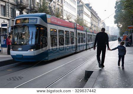 Zurich, Switzerland - Oct 24, 2019: Electric Blue Tram In The City Center Of Zurich With Local Peopl