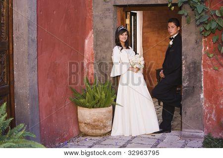 Hispanic girl in Quinceanera dress with chamberlain