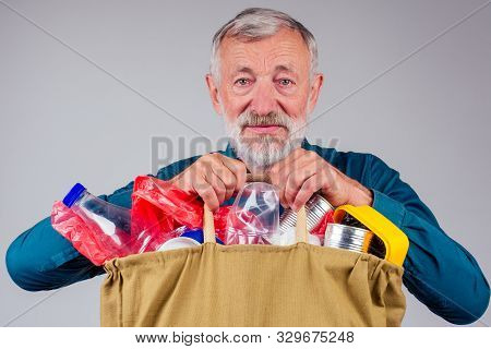 Old Grandfather Holding Cotton Eco Bag Full Of Garbage In Studio White Background