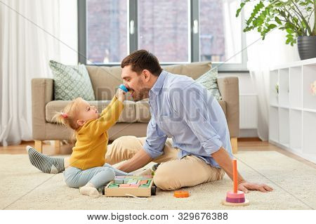 family, fatherhood and people concept - happy father and little baby daughter playing with wooden toy toy blocks kit at home poster