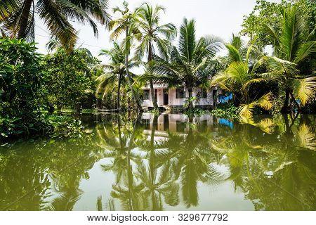 House In The Kerala Backwaters In The Lush Jungle Along The Canal With Bright Reflections, Alappuzha