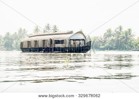 House Boat On The River Of The Kerala Backwaters Along Palm Trees In Bright Sunlight, Alleppey - Ala