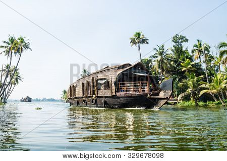 Line Of House Boats With Reflections On The Water On The River Of The Kerala Backwaters Along Palm T