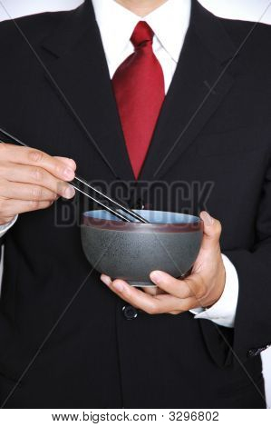 Business man in black suit and red power tie eating from a Japanese bowl with chopsticks. poster
