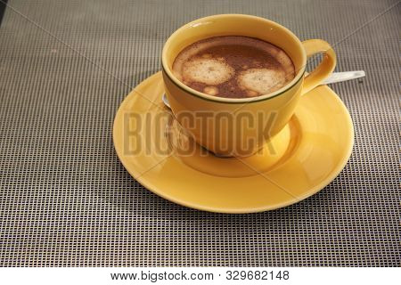 A Yellow Cup Of Tasty Brown Coffee And Spoon On The Table In Restuarant