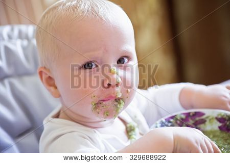 Little Beautiful Baby Girl With A Blurred Broccoli Face. A One-year-old Child Eats Himself With A Sp