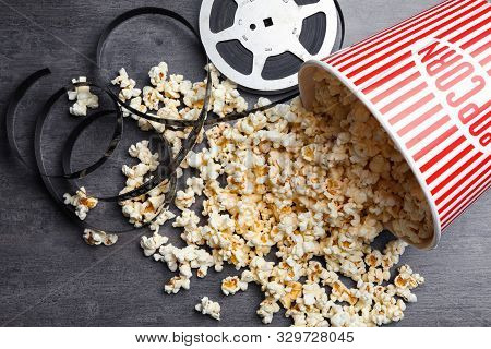 Popcorn And Movie Reel On Grey Stone Table, Flat Lay. Cinema Snack