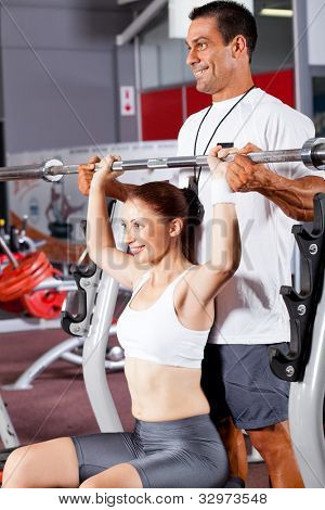 young fitness woman with personal trainer in gym