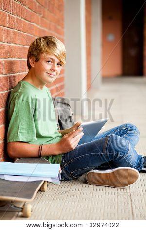 male high school teen student using tablet computer in school