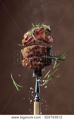 Grilled Ribeye Beef Steak With Rosemary On A Brown Background. Beef Steak On A Fork Sprinkled With R