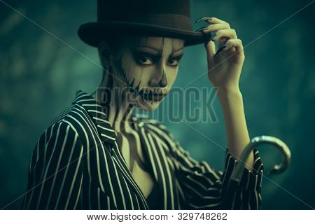 Elegant young woman in a male tailcoat and top-hat with pumpkin skull make-up. Pumpkin queen. Costumes and makeup for Halloween.