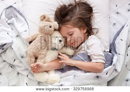 Sweet Little Girl Sleeping With Toys In Crib. Close Up Portrait Of Infant Sleeping In Cot. Beautiful