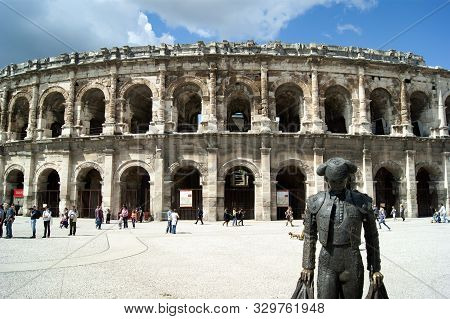 Nimes / France / April 4  2011: Arena Of Nimes. A Perfectly Preserved Roman Amphitheatre. A Statue O
