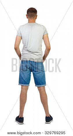 Back view of young manin shorts looking. Rear view people collection. backside view of person. Isolated over white background. A guy in denim shorts stands with his hands in his pockets.