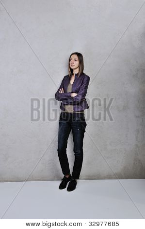 Pretty young woman standing daydreaming and romanticising her fantasies over grey background