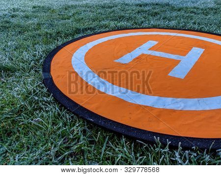 Orange Helipad Landing Pad For Drones Laying In Frosty Grass