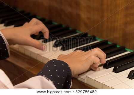 Close Up Of Child Hands Playing The Piano. Selective Focus. Warm Shade. Boy Fingers And Beautiful Sh
