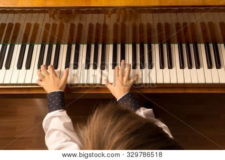Top View Of A Little Boy Playing The Piano. Head And Hands In White Shirt In The Frame. Selective Fo