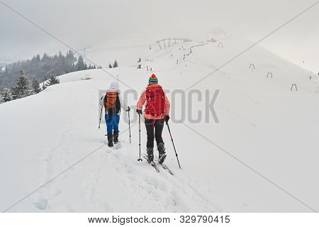 Two Women Friends Hiking And Ski Touring Side By Side On A Ridge, With Overcast Sky, Above Azuga Ski