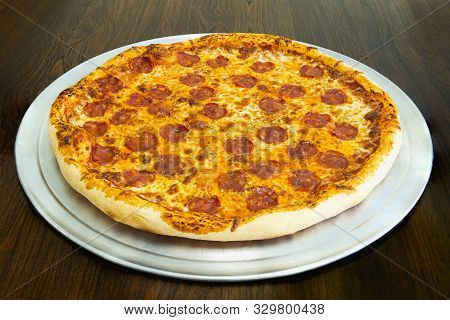 Fresh Pepperoni Pizza On Woooden Table In Restaurant.